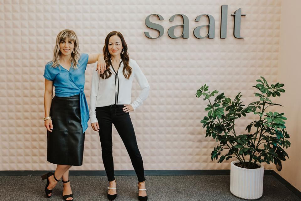 Fawson and Hoeger stand in front of sign reading Saalt.
