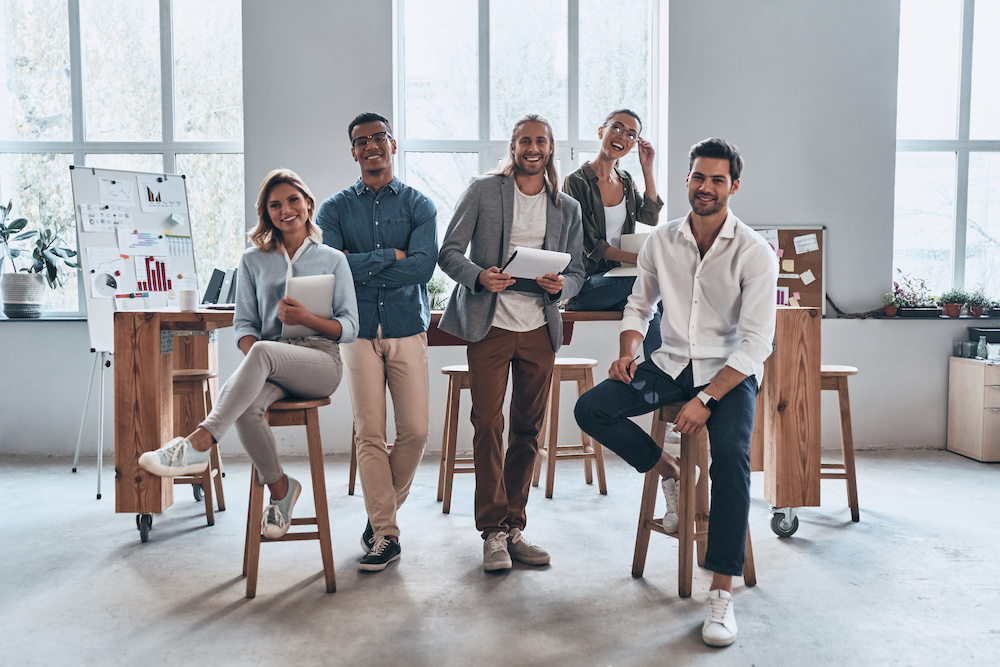 Young business professionals. Full length of young modern people in smart casual wear smiling and looking at camera while standing in the creative office